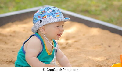 Baby boy digging in the sandbox. Smiles and touches the sand