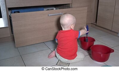 Baby boy doing mess in kitchen. Child play with bowls and ...