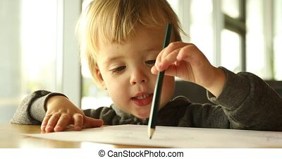 Baby boy draws with a pencil