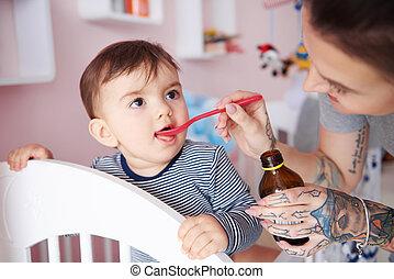 Baby boy drinking medicine off a spoon