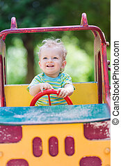 Baby boy driving a toy car at the playground