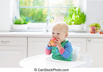 Baby boy eating apple in white kitchen at home