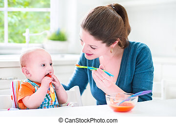Baby boy eating his first solid food
