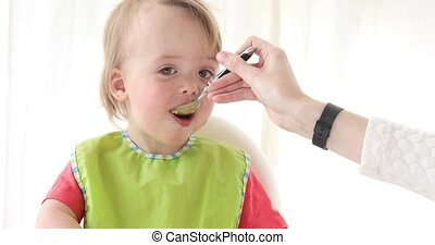Baby boy feeding with a spoon