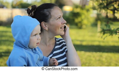 Baby boy hold by mother in the park. Mum calling at the phone.