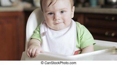 Baby boy in a children's chair
