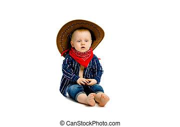 boy in a cowboy hat sitting on a white floor