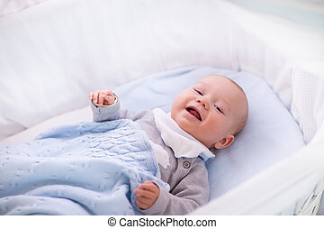 Baby boy in a crib under knitted blanket - Newborn baby boy...