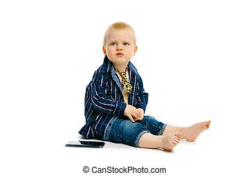 boy in a tie sitting on a white floor