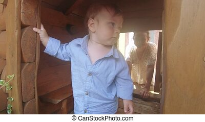 Baby boy in a wooden house