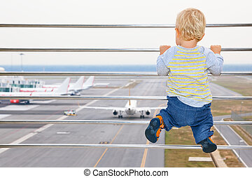 Baby boy in airport transit hall looking at airplane -...