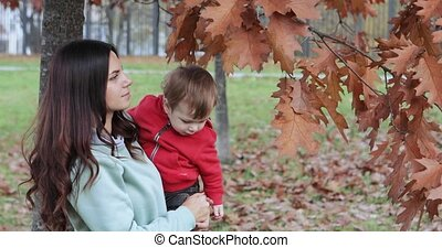 Baby boy in autumn city park