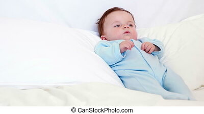 Baby boy in blue babygro lying on p