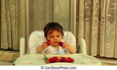 Baby boy in highchair eating strawberries making mess...