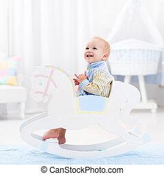 Baby boy in rocking horse toy