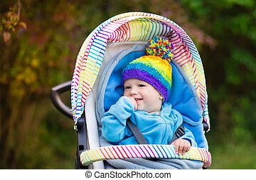 Baby boy in stroller in autumn park