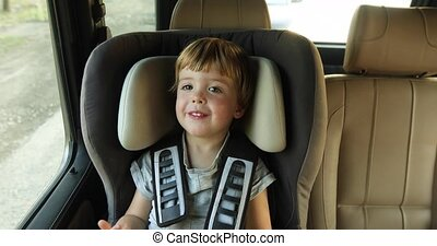baby boy in the children's car seat in the car. Kid smiles