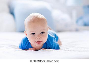 Baby boy in white sunny bedroom