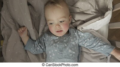 Baby boy is lying in a cot and is chattering. Kid in the...