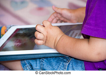 Baby boy is sitting on floor playing with tablet pc. Close-up photo of the hands. Little   touch pad, early learning.