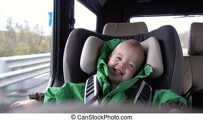 Baby boy laughs in the car in the chair