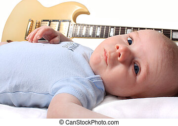 Baby boy laying with guitar