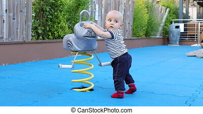 Baby Boy Learning To Stand At The Outdoor Playground