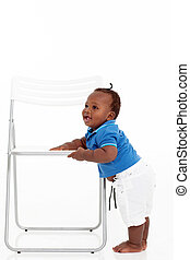 baby boy learning to walk around a chair - cute african...