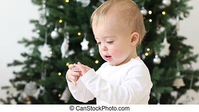 Baby boy looking at toys on the Christmas tree