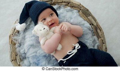baby boy lying in a basket with fur hat-knitting