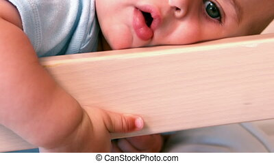 Baby boy lying in crib in slow motion
