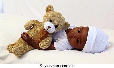 Baby boy lying in crib with teddy bear at home in bedroom