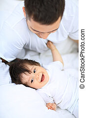 Baby boy lying on bed, next to his father
