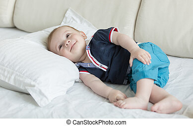 Baby boy lying on big pillow on bed