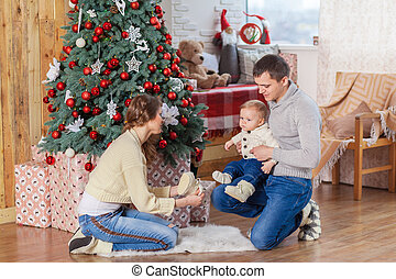 Baby boy near christmas decorated tree with parents