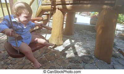 Baby boy on a wooden swing