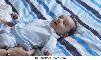 Baby boy on bed - Baby boy is lying on his daddy's bed, who...