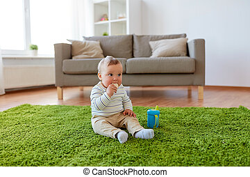 childhood, kids and people concept - baby boy sitting on floor with sippy cup and eating rice cracker at home