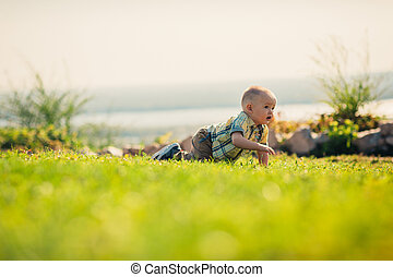 Baby boy on green grass nature background