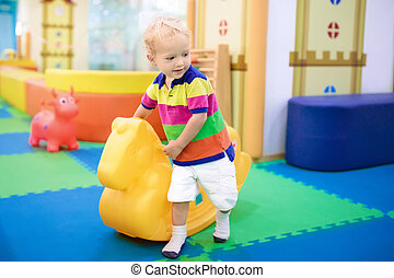 Baby boy on swing at day care play room. Kids play