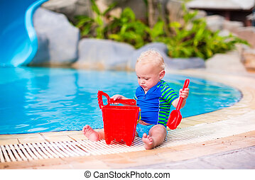 Baby boy playing at a pool