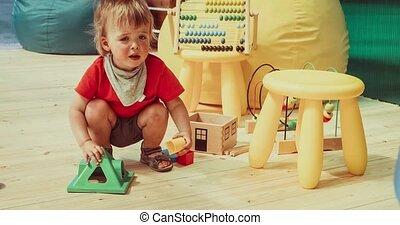 Baby boy playing colorful blocks sitting on floor