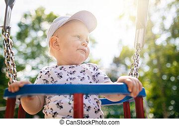 Baby boy playing in playground having fun