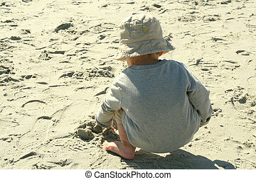Baby boy playing in the sand