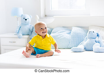 Baby boy playing on bed in sunny nursery - Baby playing on...