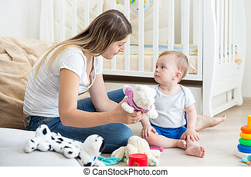 Baby boy playing on floor at living room with mother
