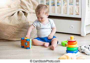 Baby boy playing on floor with colorful toy car