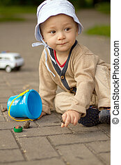 Baby Boy Playing on the Ground in The Park. Summer or spring activity for child