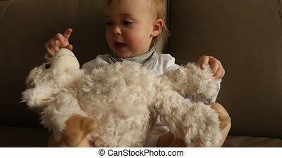 Baby boy playing soft toy on sofa