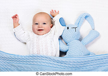 Baby boy playing with blue knitted bunny toy - Funny little...